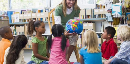 Teacher in class showing students a globe